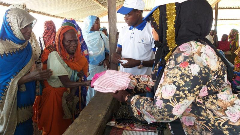 Najwa Adam donating new clothing to a group of women refugees in Africa. The women is reaching her hand out to receive the pink piece of clothing.